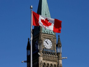 A Canadian flag flies in front of the Peace Tower on Parliament Hill in Ottawa.
