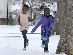 Seven year-old Abuk Garng (R) and her best friend six year-old Arek Kuot are seen embracing the winter weather in front of their home along 8th Ave. SW. Sunday, April 18, 2021.