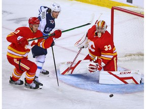 Calgary Flames goaltender David Rittich keeps his eyes on a puck with the Winnipeg Jets' Mark Scheifele and the Flames' Mikael Backlund at the Saddledome in Calgary on Saturday, March 27, 2021.