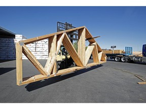 A worker loads finished trusses for homes onto a truck at Wasatch Truss in Utah. Lumber prices have sky rocketed along with supply shortages the last several months have plagued the construction industry.
