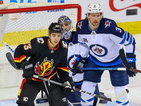 The Calgary Flames' Johnny Gaudreau and Winnipeg Jets' Tucker Poolman fight for position in front of Jets goaltender Connor Hellebuyck at the Saddledome in Calgary on Friday, March 26, 2021.