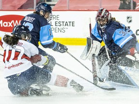 Team Scotiabank'sRhianna Kurio drives to the net as Team Bauer'sCatherine Daoust and goaltenderAnn-Renee Desbiens defend during thePWHPA Secret Dream Gap Tour at the Saddledome in Calgary on Friday, May 28, 2021.