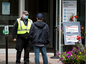 A client checks in at the entrance to the Telus Convention Centre COVID-19 vaccination clinic on Thursday, June 10, 2021.