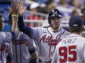 MIAMI, FL - JULY 11: Freddie Freeman #5 of the Atlanta Braves is congratulated by teammates after scoring in the fourth inning against the Miami Marlins at loanDepot park on July 11, 2021 in Miami, Florida.