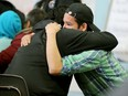 A young man gets a hug from a friend during talk of recent events in Attawapiskat First Nation. (JULIE OLIVER/POSTMEDIA)