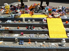 Children's shoes and stuffed animals are placed on the steps of Calgary City Hall on June 1, 2021, to commemorate the discovery of 215 children found buried at a former residential school in Kamloops, B.C.