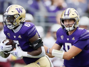SEATTLE, WASHINGTON - SEPTEMBER 04: Dylan Morris #9 hands off the ball to Richard Newton #6 of the Washington Huskies during the first quarter against the Montana Grizzlies at Husky Stadium on September 04, 2021 in Seattle, Washington.