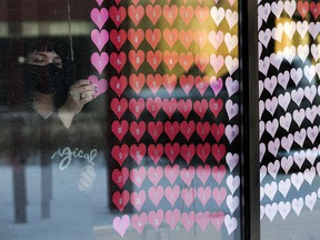 Sara Edwards adds more paper hearts, one for every Albertan who has died from COVID-19, to a memorial at All Saints' Anglican Cathedral in Edmonton on Jan. 29, 2021.