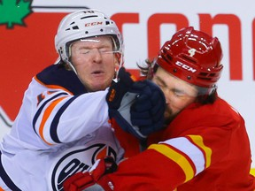 Edmonton Oilers Tyler Benson collides with Rasmus Andersson of the Calgary Flames during pre-season NHL hockey in Calgary on Sunday, September 26, 2021. AL CHAREST / POSTMEDIA