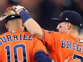 Houston Astros Yuli Gurriel and Alex Bregman celebrate the team's 7-2 win over the Atlanta Braves in Game 2 of the World Series at Minute Maid Park on Wednesday in Houston.