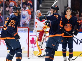 The Edmonton Oilers' Connor McDavid celebrates a goal on Calgary Flames goaltender Jacob Markstrom with teammates at Rogers Place in Edmonton on Saturday, Oct. 16, 2021.