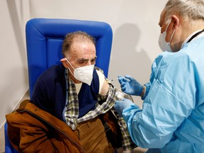 An elderly man receives a dose of the Moderna vaccine against COVID-19 at the Music Auditorium in Rome, Feb. 15, 2021.