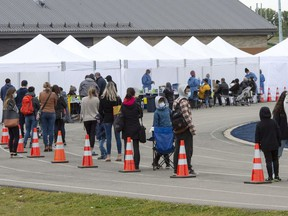 People line up at a COVID-19 testing site in St. Lambert, Que. on Friday, September 25, 2020.