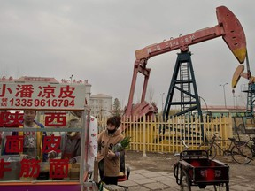 This picture taken on May 2, 2016 shows local residents buying noodle soup next to oil pumps in Daqing, Heilongjiang province.