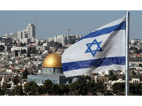 The Israeli flag flutters in front of the Dome of the Rock mosque and th city of Jerusalem, on December 1, 2017.  Two Israeli cabinet ministers said on November 30 that they hoped US President Donald Trump was about to move his country's embassy from Tel Aviv to Jerusalem, as a decision deadline neared. The issue is deeply controversial. Shifting the building could be seen as a de facto recognition of Israel's claim over the whole city, including predominantly Palestinian east Jerusalem.