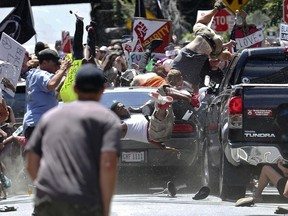 In this Aug. 12, 2017 file photo, people fly into the air as a vehicle is driven into a group of protesters demonstrating against a white nationalist rally in Charlottesville, Va.