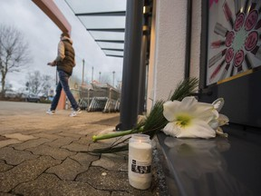 A man lays down flowers at the entrance of the drugstore in Kandel, Germany, Thursday, Dec. 28, 2017.