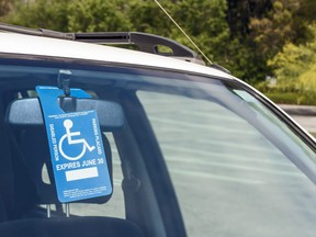 In this stock photo, a disabled parking permit hangs in the windshield of a car in a parking lot.