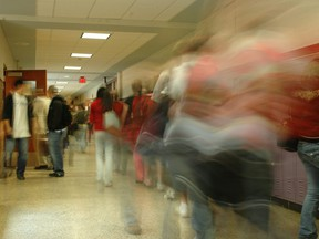 In this stock photo, high school students walk down a hallway.