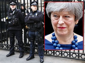 Police officers guard the gates to Downing Street in London, Wednesday, Dec. 6, 2017. Two men will appear in a London court to face terror charges Wednesday after reportedly plotting to assassinate British Prime Minister Theresa May. The plan, revealed to the British Cabinet on Tuesday, allegedly involved planting a bomb outside the entrance to Downing Street gates before attackers would stab the U.K. leader in the ensuing chaos. (AP Photo/Kirsty Wigglesworth)
