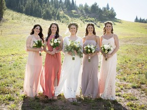 In this Sept. 2, 2017 photo provided by Nisha Louise, Alison Reed, center, of Colorado Springs, Colo., stands with her bridal party in Vail, Colo. Reed chose to allow her bridesemaids leeway in the colors and styles of dresses they wore. Experts say mismatched bridesmaids dresses are a growing trend as more brides personalize their weddings. (Nisha Louise Photography via AP) ORG XMIT: NYLS412  AP PROVIDES ACCESS TO THIS THIRD PARTY PHOTO SOLELY TO ILLUSTRATE NEWS REPORTING OR COMMENTARY ON FACTS DEPICTED IN IMAGE; MUST BE USED WITHIN 14 DAYS FROM TRANSMISSION; NO ARCHIVING; NO LICENSING; MANDATORY CREDIT