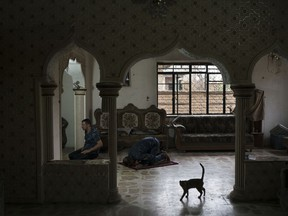 In this Nov. 9, 2017, photo, Federal policemen pray inside an abandoned house used as a temporary base in the hospital complex where the morgue was located in Mosul, Iraq. Much of the complex was destroyed in fighting to wrest the city from Islamic State group militants earlier this year.