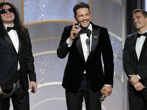 """This image released by NBC shows James Franco, center, accepting the award for best actor in a motion picture comedy or musical for his role in """"The Disaster Artist,"""" as Tommy Wiseau, left, and brother Dave Franco look on at the 75th Annual Golden Globe Awards in Beverly Hills, Calif., on Sunday, Jan. 7, 2018. (Paul Drinkwater/NBC via AP)"""