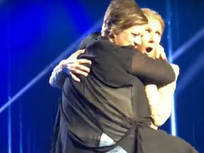 An unnamed woman awkwardly hugs Céline Dion on stage during the singer's Jan. 5 concert in Las Vegas, Nevada. (Mat's Channel/YouTube)