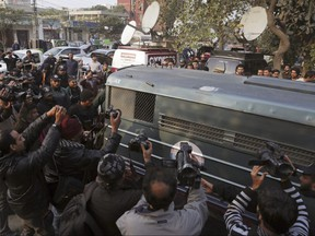 Surrounded by journalists and security forces, a prison van carrying Mohammad Imran, who is accused of the brutal killings of eight children in Kasur, arrives to a courthouse, in Lahore, Pakistan, Wednesday, Jan. 24, 2018.