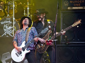 """Motorhead's lead singer Ian """"Lemmy"""" Kilmister (R) and lead guitarist Phil Campbell perform with the band on the Pyramid Stage on the first official date of the Glastonbury Festival of Music and Performing Arts on Worthy Farm near the village of Pilton in Somerset, south west England, in this June 26, 2015 file photo. (OLI SCARFF/AFP/Getty Images)"""
