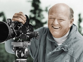 In this undated photo provided by the Warren Miller Co., Warren Miller is shown posing for a photo with a film camera. (Warren Miller Co. via AP)