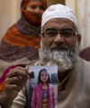 In this Thursday, Jan. 18, 2018 photo, Mohammed Amin holds a picture of his daughter Zainab Ansari as her mother Nusrat stands in the background in Kasur, Pakistan. A provincial government official says they have arrested a man they suspect raped and killed 7 year-old Zainab, the child whose horrific death enraged a nation and lifted the silence that surrounds child sexual abuse in Pakistan. (AP Photo/B.K. Bangash)