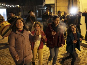 Children smoke while walking with a music band in the village of Vale de Salgueiro, northern Portugal, during the local Kings' Feast Friday night, Jan. 5, 2018. The village's Epiphany celebrations, called Kings' Feast, feature a tradition that each year causes an outcry among outsiders: parents encourage their children, some as young as 5, to smoke cigarettes.