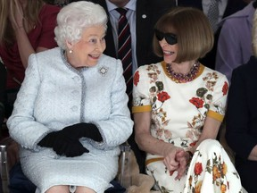 Britain's Queen Elizabeth sits next to fashion editor Anna Wintour as they view Richard Quinn's runway show before presenting him with the inaugural Queen Elizabeth II Award for British Design, as she visits London Fashion Week's BFC Show Space in central London, Tuesday, Feb. 20, 2018. (Yui Mok/Pool photo via AP) ORG XMIT: LON112