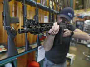 Dordon Brack, aims a semi-automatic AR-15 that is for sale at Good Guys Guns & Range on February 15, 2018 in Orem, Utah. An AR-15 was used in the Marjory Stoneman Douglas High School shooting in Parkland, Florida. (Photo by George Frey/Getty Images)