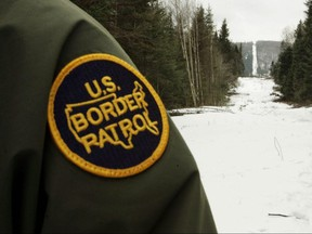 A U.S. Border Patrol agent stands along the boundary marker cut into the forest marking the line between Canada on the right and the United States on March 23, 2006 near Beecher Falls, Vermont.