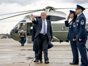U.S. President Donald Trump waves as he boards Air Force One at Andrews Air Force Base, Md., Friday, Feb. 16, 2018, to travel to Palm Beach International Airport in West Palm Beach, Fla. (AP Photo/Andrew Harnik)