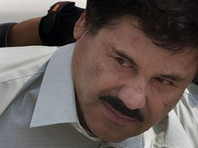 """In this Feb. 22, 2014 file photo, Joaquin """"El Chapo"""" Guzman is escorted to a helicopter in handcuffs by Mexican navy marines at a navy hanger in Mexico City. (AP Photo/Eduardo Verdugo, File)"""