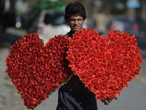 A Pakistani vendor carries heart-shaped bouquets for sale ahead of Valentine's Day along a street in Islamabad on Feb. 13, 2017.