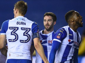 Wigan Athletic striker Will Grigg celebrates with teammates after scoring his team's first goal during the English FA Cup fifth round match against Manchester City at the DW Stadium in Wigan on February 19, 2018. (OLI SCARFF/Getty Images)
