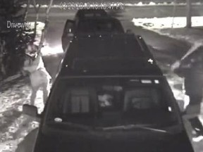 This screenshot of a video released by the Royal Newfoundland Constabulary shows a pair of vandals smashing a truck's windows in St. John's, N.L.