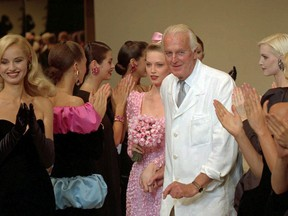 """FILE - In this July 11 1995 file photo, French designer Hubert de Givenchy is applauded by his models after his 1995-96 fall-winter haute couture fashion collection in Paris. French couturier Hubert de Givenchy, a pioneer of ready-to-wear who designed Audrey Hepburn's little black dress in """"Breakfast at Tiffany's,"""" has died at the age of 91."""