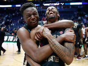 Mfiondu Kabengele of the Florida State Seminoles celebrates with Braian Angola after defeating the Xavier Musketeers in the second round of the 2018 NCAA basketball tournament at Bridgestone Arena on March 18, 2018