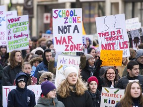 People hold up signs during a 'March of Our Lives' rally to show solidarity with the U.S. gun control movement in Montreal, Saturday, March 24, 2018. THE CANADIAN PRESS/Graham Hughes