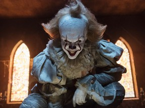 """This image released by Warner Bros. Pictures shows Bill Skarsgard as the evil clown Pennywise in a scene from the film """"It,"""" based on the book by Stephen King."""