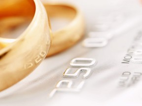 In this stock photo, wedding rings lay on top of a credit card.
