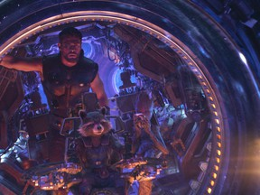 """This image released by Marvel Studios shows Chris Hemsworth as Thor. with characters Rocket, voiced by Bradley Cooper, seated center, and Groot, voiced by Vin Diesel, in a scene from """"Avengers: Infinity War."""" (Marvel Studios via AP)"""