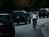 (FILES) This file photo taken on October 28, 2017 shows a woman on a bike gestures with her middle finger as a motorcade with US President Donald Trump departs Trump National Golf Course in Sterling, Virginia. Juli Briskman didn't think twice when she gave President Donald Trump the finger as his motorcade passed her while she was cycling on a road near his golf club. But the obscene gesture, captured on October 28 by AFP White House photographer Brendan Smialowski, who was riding in Trump's convoy, quickly went viral. And it has now cost the single mom her job. / AFP PHOTO / Brendan SmialowskiBRENDAN SMIALOWSKI/AFP/Getty Images