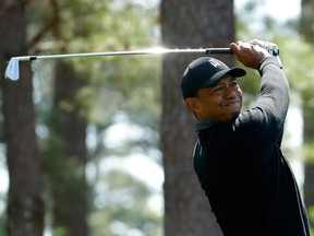 In this April 5, 2018, file photo, Tiger Woods hits a shot on the fourth hole during the first round at the Masters golf tournament in Augusta, Ga.