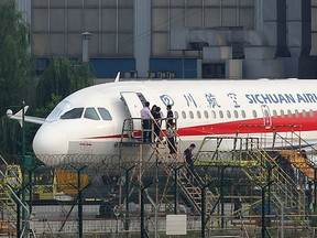 This photo taken on May 14, 2018 shows employees checking a Sichuan Airlines Airbus A319 after an emergency landing, as a broken cockpit window (L) is covered, in Chengdu in China's northwestern Sichuan province. (Getty Images)